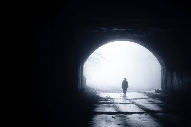 una persona esce da un tunnel in lontananza