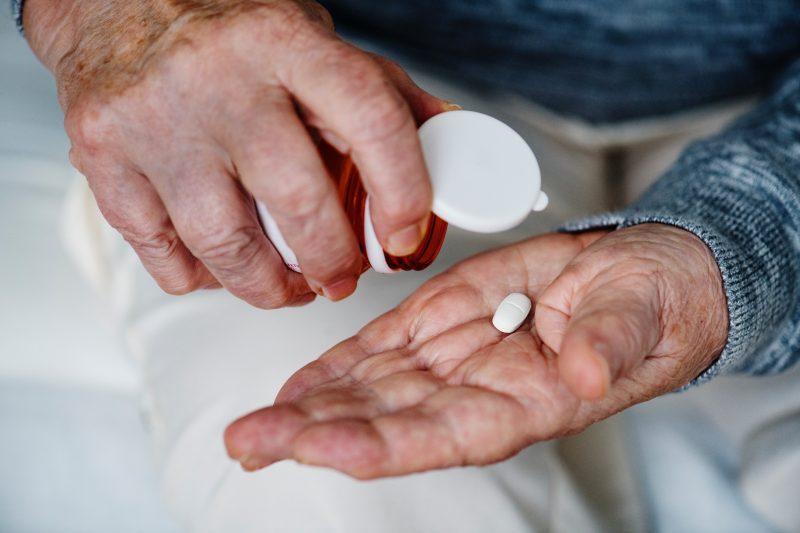 Dettaglio su mani che prendono una pastiglia da un flacone